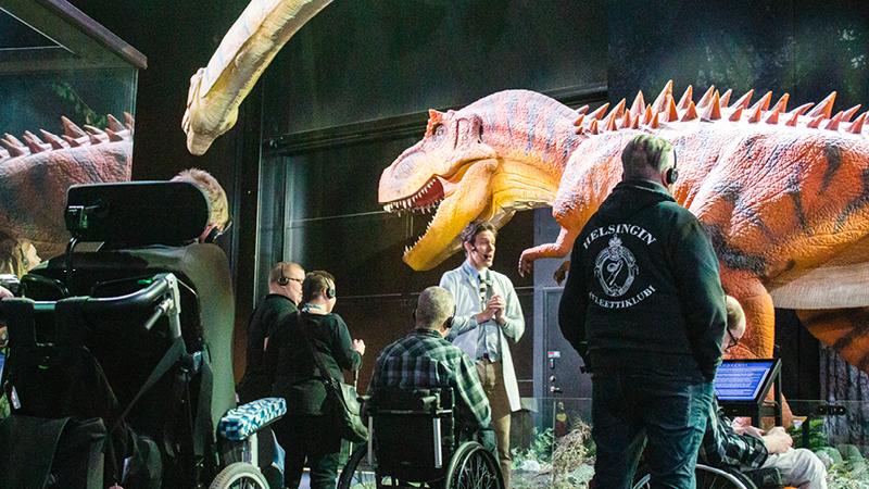 Kuvassa Elä täysii -klubilaisia esteettömällä retkellä Tiedekeskus Heurekassa. Kuvassa näkyy myös opas ja taustalla dinosauruksia.