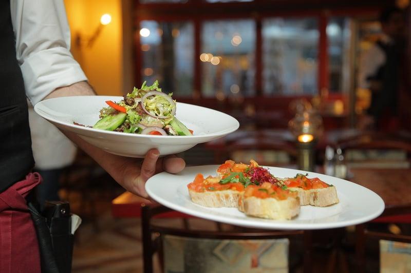 Kuvassa tarjoilija kantaa kahta lautasta, jossa toisessa salaatti ja toisessa tapaksia.