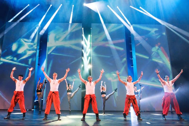 Kuvassa poikabändi musikaalin 5 näyttelijää edessä kädet ilmassa ja takana neljä tanssijaa.