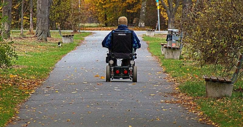 Mies ajaa sähköpyörätuolilla pitkin puiston polkua.